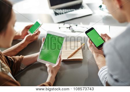Businessman and businesswoman using touchpad and smartphones