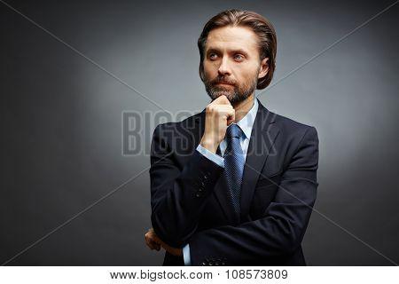 Pensive businessman looking sideways in isolation