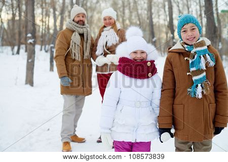 Happy siblings in winterwear looking at camera with parents on background