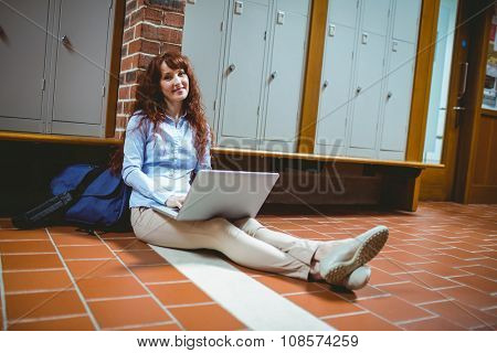 Mature student using laptop in hallway at the university
