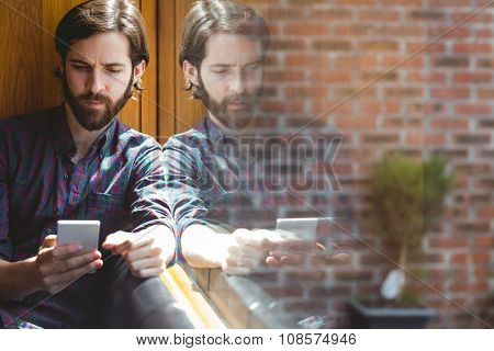 Hipster student sending text in canteen at the university