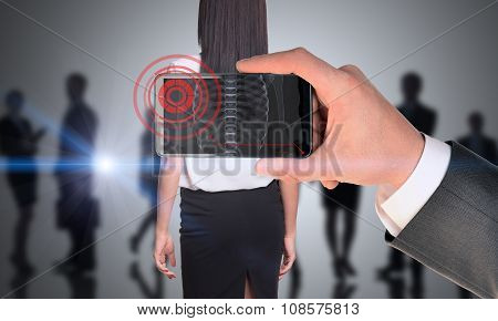 Man holding smartphone with x-ray of womans back