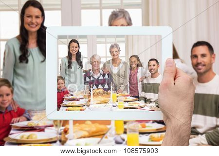 Hand holding tablet pc against happy extended family at christmas dinner posing at camera