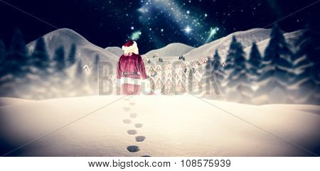 Santa carrying sack of gifts against aurora shimmering in night sky