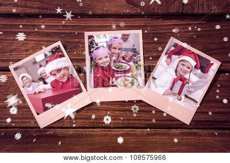 Instant photos on wooden floor against smiling daughter holding gift with her family behind