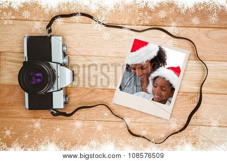 Mother and daughter opening a Christmas gift against view of an old camera