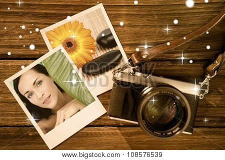 Beautiful nude brunette smiling at camera with green leaf against sunflower surrounded by black stones