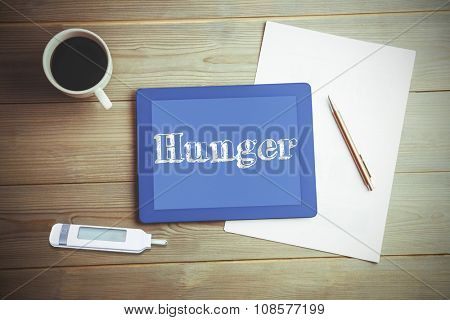 The word hunger and glucose monitor against high angle view of digital tablet and document with coffee