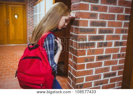 Worried student leaning against the wall at the university