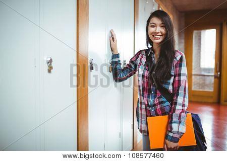 Cheerful student standing next the locker at the university