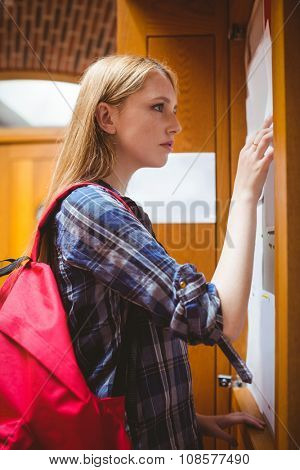 Pretty student looking at notice-board at the university