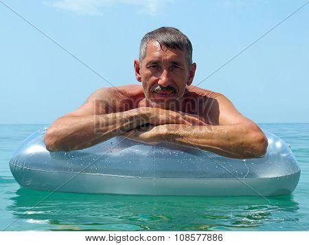 Senior man sunbathing on water mattress