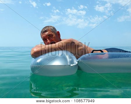 Happy senior man sunbathing on water mattress
