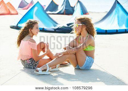 Kite surf teen girls talking in summer beach sitting on sand