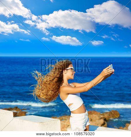Blond kid teen girl photo selfie on smartphone in a beach at Mediterranean