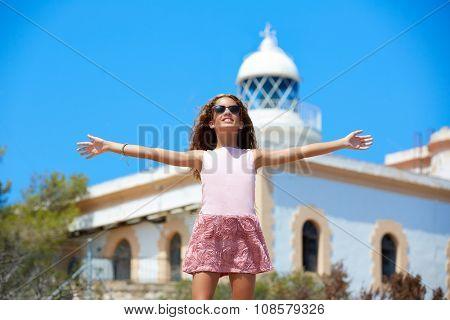 Blond girl open hands in Mediterranean Lighthouse feeling the wind in spain