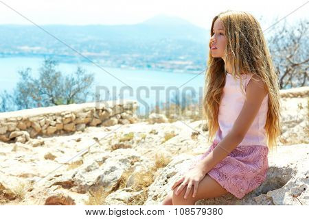 Blond girl sitting looking blue Mediterranean sea as a tourist in Spain