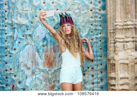 Blond teen girl tourist in Mediterranean old town door with colorful feathers on hair