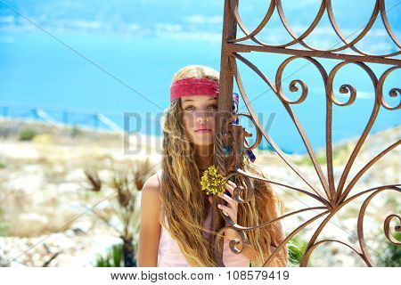 Blond girl in Mediterranean rusted gate with sea in background