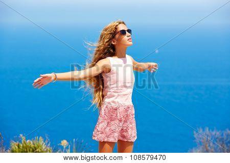 Blond girl shaking hair on air at blue Mediterranean sea tourist in Spain open hands