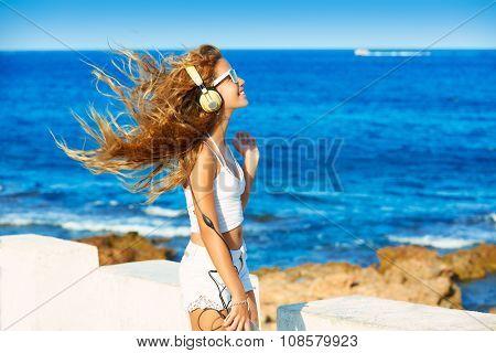 Blond kid teen girl hearing headphones music on smartphone in a beach