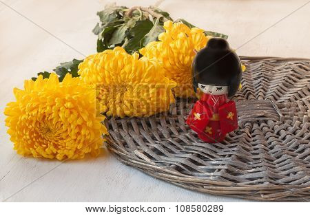 Doll Kokeshi On A Background Of Yellow Chrysanthemums  (mass Production)