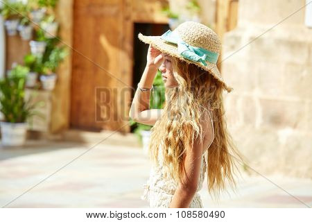 Blond teen girl tourist in Mediterranean old town profile with curly hair