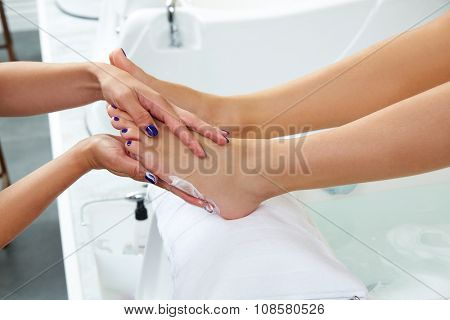 Pedicure cream treatment to woman feet in nails salon after bath