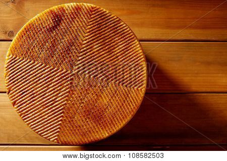 Manchego cheese from Spain in wooden table texture detail