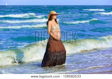 Pregnant woman on the beach playing with waves