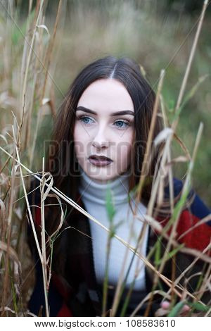 Young Woman With Long Brown Hair Looking Through Some Reeds
