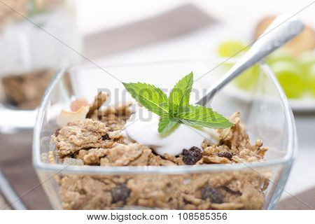 Cereals in a glass bowl on a table. Background is made of wood and light. On a top is mint