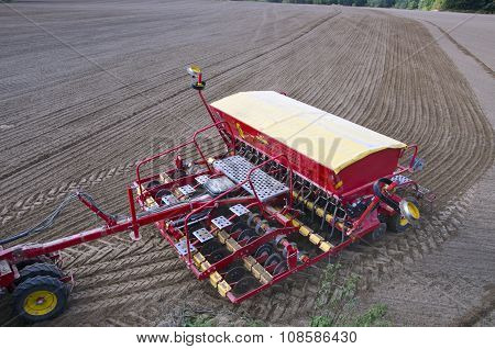 Tractor Sowing Seeds In Freshly Plowed Field