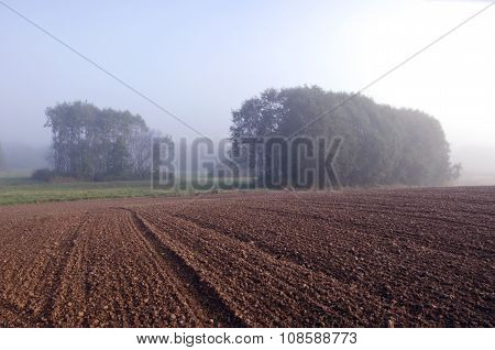Sun Rising On Freshly Plowed Clay Field In Rural Landscape In Morning