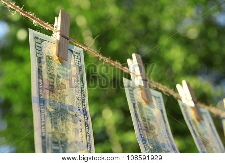 Concept of money laundering - one hundred bills hanging on a cord, outdoors