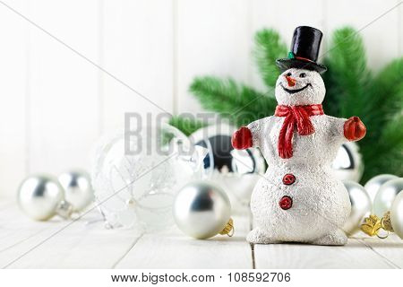 Snowman with christmas fir and balls on wooden board