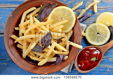 French fried potatoes in bowl with basil and sauce on old wooden background