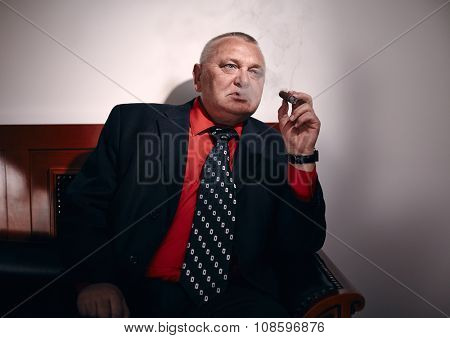 Serious middle aged businessman wearing black suit, red shirt and wristwatch sitting on old fashioned sofa in office and smoking cigar