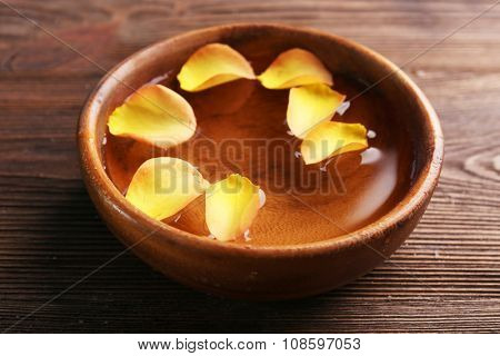 Orange rose petals in a bowl of water on wooden background