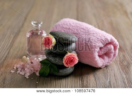 Spa composition of a towel, salt, flowers and stones, on wooden background