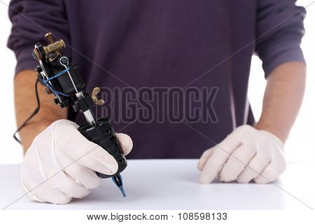 Tattoo machine in male's hand  on white background