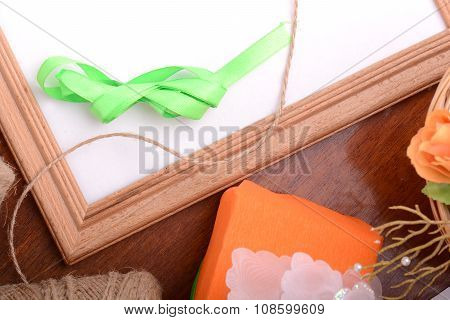 Christmas Gift Box And Empty Wooden Frame On Wooden Table