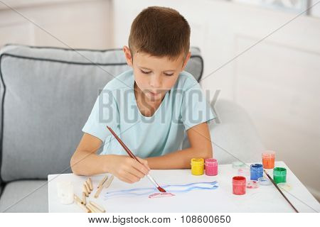 Cute little boy painting picture on home interior background
