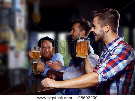 Young men drinking beer in pub