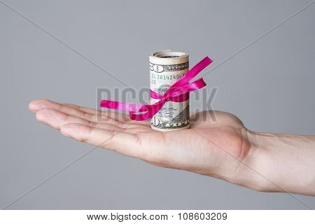 Money With Ribbon In Male Hand On A Gray Background
