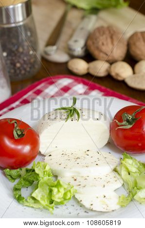 Mozzarela on a plate with salad, tomatoes on a table and nuts, knife, salt, pepper like a background
