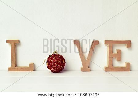 some wooden letters and a red christmas bauble forming the word love on a white scene