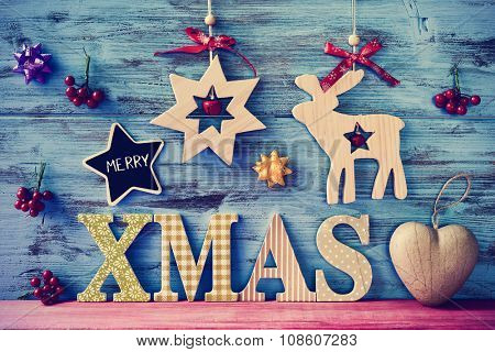 a star-shaped chalkboard with the text merry and wooden letters forming the text xmas on a blue rustic wooden surface with some different cozy christmas ornaments
