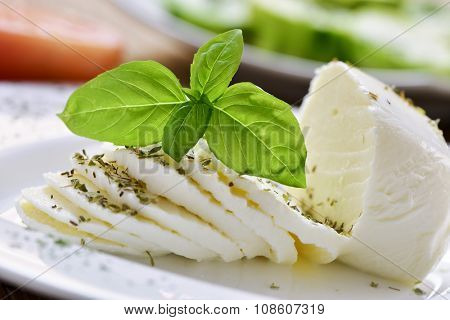 closeup of a plate with a sliced fresh cheese