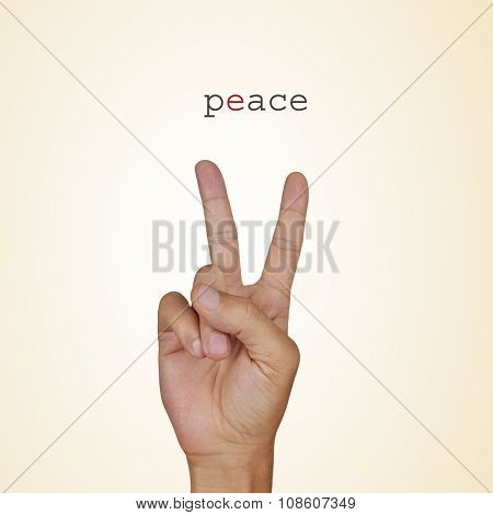 closeup of the hand of a young man giving the V sign and the word peace on a beige background